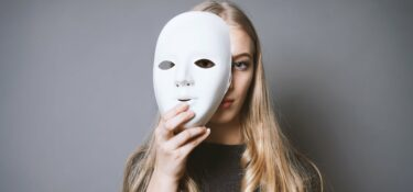 Young woman holding blank mask in front of face